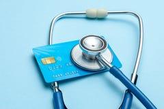 Πιστωτική κάρτα με το στηθοσκόπιο στο μπλε υπόβαθρο Η έννοια του ιατρικού strechevka ή της ακριβής ιατρικής, μισθός γιατρών στοκ φωτογραφία με δικαίωμα ελεύθερης χρήσης