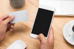 Πιστωτική κάρτα χεριών εκμετάλλευσης επιχειρηματιών και χρησιμοποίηση του smartphone Στοκ Φωτογραφία