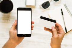 Πιστωτική κάρτα χεριών εκμετάλλευσης και χρησιμοποίηση του smartphone Μια μαύρη χλεύη smartphone επάνω και μια πιστωτική κάρτα στ Στοκ Εικόνα
