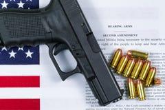 Πιστόλι με τη σημαία και αμερικανικό έγγραφο για το δικαίωμα να αντεχτούν τα όπλα Στοκ Φωτογραφίες