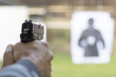 Πιστόλι πυρκαγιών ατόμων στο στόχο στη σειρά πυροβολισμού Στοκ Φωτογραφία