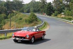 Πιό στενό επάνω κλασικό μικρό κόκκινο ιταλικό αθλητικό αυτοκίνητο προς τα κάτω στο δρόμο στοκ φωτογραφία