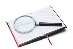 πιό magnifier σημειωματάριο χεριών Στοκ Φωτογραφία