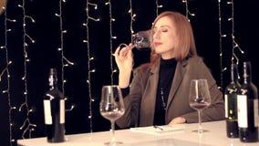Πιό sommelier δοκιμάζοντας κρασί γυναικών και γράψιμο κάτω των εντυπώσεων σε ένα σημειωματάριο φιλμ μικρού μήκους