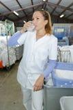Πλάγιας όψης πολυάσχολο πόσιμο νερό εργαζομένων πλυντηρίων θηλυκό στοκ εικόνα