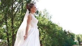 Πλάγια όψη από κάτω από μιας νέας ευτυχούς νύφης σε ένα άσπρο φόρεμα απόθεμα βίντεο