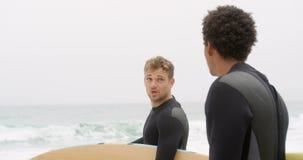 Πλάγια όψη δύο αρσενικών surfers που στέκεται με την ιστιοσανίδα στην παραλία 4k απόθεμα βίντεο