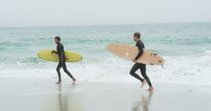 Πλάγια όψη δύο αρσενικών surfers που τρέχει με την ιστιοσανίδα στην παραλία 4k απόθεμα βίντεο