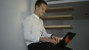 Πλάγια όψη ενός νέου επαγγελματικού ατόμου freelancer στο άσπρο πουκάμισο που χρησιμοποιεί έναν φορητό προσωπικό υπολογιστή καθμέ απόθεμα βίντεο