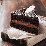 Πλάγια όψη κέικ σοκολάτας σχετικά με ένα αγροτικό ύφος πινάκων κοπής στοκ φωτογραφία με δικαίωμα ελεύθερης χρήσης