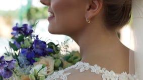 Πλάγια όψη κινηματογραφήσεων σε πρώτο πλάνο μιας όμορφης ευτυχούς νύφης γυναικών με μια κομψή ανθοδέσμη απόθεμα βίντεο