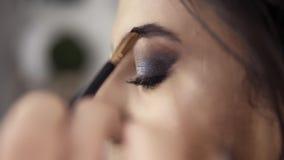 Πλάγια όψη κινηματογραφήσεων σε πρώτο πλάνο των χεριών καλλιτεχνών ` s makeup που χρησιμοποιούν τη βούρτσα στα φρύδια χρωμάτων γι φιλμ μικρού μήκους