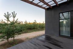 Πλάγια όψη μιας ανοικτής βεράντας μπροστά από ένα σύγχρονο δασικό εξοχικό σπίτι Νέο δάσος πεύκων κάτω από τις ακτίνες ηλιοβασιλέμ Στοκ Φωτογραφία