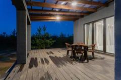 Πλάγια όψη μιας ανοικτής βεράντας μπροστά από ένα σύγχρονο δασικό εξοχικό σπίτι Νέο δάσος πεύκων κάτω από τις ακτίνες ηλιοβασιλέμ Στοκ Εικόνες