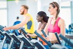 Πλάγια όψη μιας κατάλληλης ευτυχούς γυναίκας και της εκπαιδευτικής ομάδας της σχετικά με treadmill Στοκ Φωτογραφίες