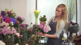 Πλάγια όψη μιας νέας ελκυστικής γυναίκας στην ποδιά που λειτουργεί στο floral κατάστημα και που τακτοποιεί τη δέσμη του λουλουδιο απόθεμα βίντεο