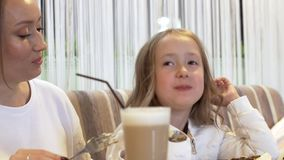 Πλάγια όψη - μια χαριτωμένη νέα μητέρα και μια χαριτωμένη μικρή κόρη τρώνε από κοινού απόθεμα βίντεο