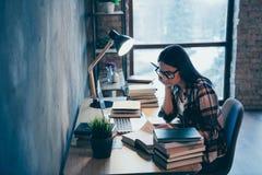 Πλάγια όψη σχεδιαγράμματος της συμπαθητικής ελκυστικής έξυπνης έξυπνης ευφυούς κυρίας brunette στο ελεγχμένο πουκάμισο που ερευνά στοκ εικόνες