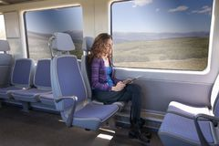Πλάγια όψη της γυναίκας στο τραίνο που διαβάζει την ψηφιακή ταμπλέτα Στοκ Φωτογραφία