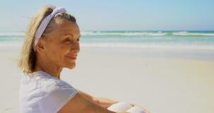 Πλάγια όψη της ενεργού ανώτερης καυκάσιας γυναίκας που εκτελεί τη γιόγκα στην παραλία 4k φιλμ μικρού μήκους