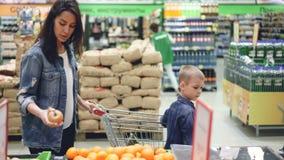 Πλάγια όψη της εύθυμης οικογένειας mom και του περπατήματος γιων στην υπεραγορά με το καροτσάκι αγορών που επιλέγει τα φρούτα και απόθεμα βίντεο