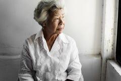 Πλάγια όψη της ηλικιωμένης ασιατικής γυναίκας με τη στοχαστική έκφραση προσώπου στοκ φωτογραφία