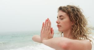 Πλάγια όψη της καυκάσιας γυναίκας που εκτελεί τη γιόγκα στην παραλία 4k φιλμ μικρού μήκους