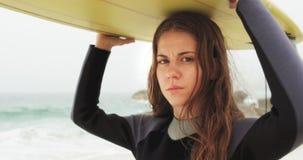 Πλάγια όψη της καυκάσιας θηλυκής φέρνοντας ιστιοσανίδας surfer στο κεφάλι της στην παραλία 4k φιλμ μικρού μήκους