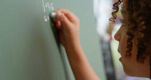 Πλάγια όψη της μαθήτριας αναμιγνύω-φυλών που λύνει math το πρόβλημα στον πίνακα κιμωλίας στην τάξη στο σχολείο 4k φιλμ μικρού μήκους