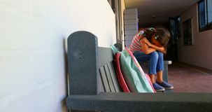 Πλάγια όψη της μαθήτριας αφροαμερικάνων με το κεφάλι κάτω από τη συνεδρίαση μόνο στον πάγκο στο σχολικό διάδρομο 4k απόθεμα βίντεο