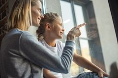 πλάγια όψη της μητέρας και της κόρης που φαίνονται έξω παράθυρο από κοινού Στοκ φωτογραφία με δικαίωμα ελεύθερης χρήσης