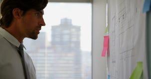 Πλάγια όψη της νέας καυκάσιας αρσενικής εκτελεστικής εργασίας στο σχεδιάγραμμα στον πίνακα γυαλιού στο σύγχρονο γραφείο 4k απόθεμα βίντεο