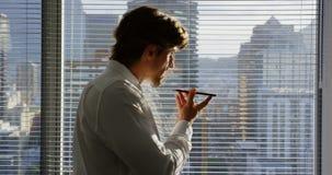 Πλάγια όψη της νέας καυκάσιας αρσενικής εκτελεστικής ομιλίας στο κινητό τηλέφωνο κοντά στο παράθυρο στο σύγχρονο γραφείο 4k φιλμ μικρού μήκους