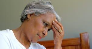 Πλάγια όψη της παλαιάς μαύρης ανώτερης συνεδρίασης γυναικών στο κρεβάτι με το χέρι στο μέτωπο στο άνετο σπίτι 4k απόθεμα βίντεο