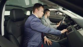 Πλάγια όψη της συνεδρίασης πελατών και πωλητών δύο ατόμων στο όμορφο αυτοκίνητο στα μπροστινά καθίσματα και της ομιλίας σχετικά μ φιλμ μικρού μήκους