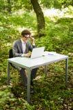 Πλάγια όψη της όμορφης εργασίας διευθυντών στο lap-top στον πίνακα γραφείων στο πράσινο πάρκο χρυσή ιδιοκτησία βασικών πλήκτρων ε Στοκ φωτογραφία με δικαίωμα ελεύθερης χρήσης