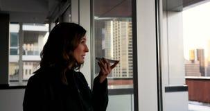 Πλάγια όψη της όμορφης καυκάσιας επιχειρηματία που μιλά στο κινητό τηλέφωνο σε ένα σύγχρονο ξενοδοχείο 4k φιλμ μικρού μήκους