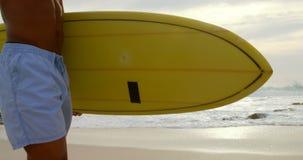 Πλάγια όψη του αρσενικού αφροαμερικάνων surfer που περπατά με την ιστιοσανίδα στην παραλία 4k απόθεμα βίντεο