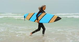 Πλάγια όψη του δραστήριου ανώτερου θηλυκού αφροαμερικάνων surfer που τρέχει προς τη θάλασσα στην παραλία 4k απόθεμα βίντεο