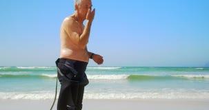 Πλάγια όψη του δραστήριου ανώτερου καυκάσιου αρσενικού surfer που στέκεται στην παραλία 4k απόθεμα βίντεο