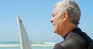 Πλάγια όψη του ενεργού ανώτερου καυκάσιου ατόμου που στέκεται με την ιστιοσανίδα στην παραλία 4k απόθεμα βίντεο