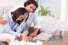 Πλάγια όψη του ζεύγους που έχει μια δυσκολία που πληρώνει τους λογαριασμούς τους στοκ εικόνα