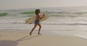 Πλάγια όψη του θηλυκού αφροαμερικάνων surfer που τρέχει με την ιστιοσανίδα στην άποψη παραλιών 4kSide Afric απόθεμα βίντεο