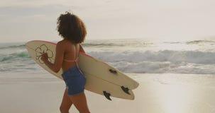 Πλάγια όψη του θηλυκού αφροαμερικάνων surfer που τρέχει με την ιστιοσανίδα στην παραλία 4k φιλμ μικρού μήκους
