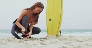 Πλάγια όψη του καυκάσιου θηλυκού λουριού ιστιοσανίδων surfer δένοντας στην ιστιοσανίδα ποδιών της στην παραλία 4k απόθεμα βίντεο