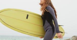 Πλάγια όψη του καυκάσιου θηλυκού surfer που τρέχει με την ιστιοσανίδα στην παραλία 4k φιλμ μικρού μήκους
