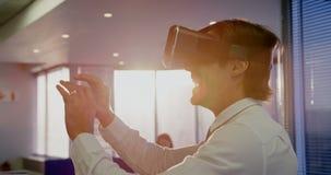 Πλάγια όψη του νέου καυκάσιου αρσενικού ανώτερου υπαλλήλου που χρησιμοποιεί την κάσκα εικονικής πραγματικότητας στο σύγχρονο γραφ φιλμ μικρού μήκους