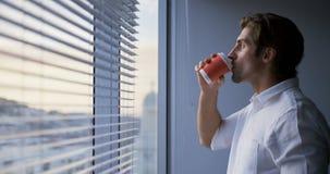 Πλάγια όψη του νέου καυκάσιου αρσενικού εκτελεστικού καφέ κατανάλωσης κοντά στο παράθυρο στο σύγχρονο γραφείο 4k απόθεμα βίντεο