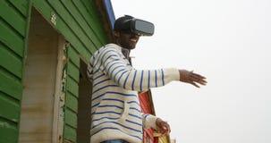 Πλάγια όψη του νέου μαύρου που χρησιμοποιώντας την κάσκα εικονικής πραγματικότητας στην καλύβα 4k παραλιών φιλμ μικρού μήκους