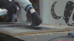 Πλάγια όψη του ξυλουργού που χρωματίζει μια ξύλινη σανίδα μέσω ενός διάτρητου, κινηματογράφηση σε πρώτο πλάνο φιλμ μικρού μήκους